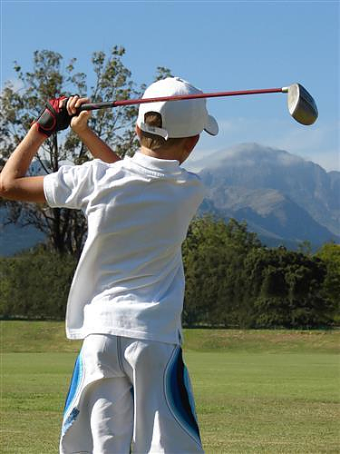 teenage boy teeing off on mountain course