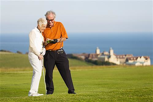 Older couple at seaside golf course marking their score