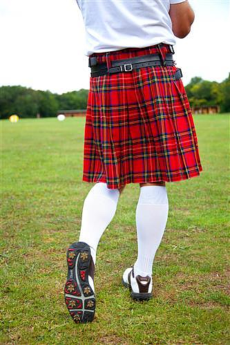 Golfer in red kilt and tall socks after a hitting a ball