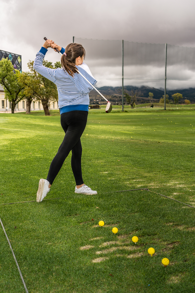 Girl practicing with a driver on cloudy autumn day