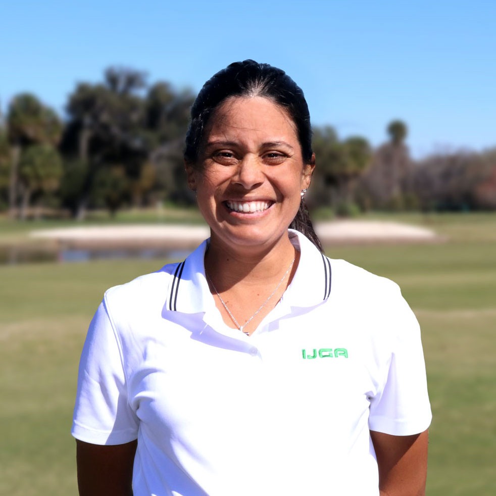 female IJGA staff with brown hair in a white shirt and green stitching