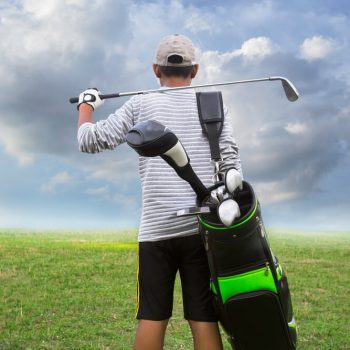 student holding golf caddy and club